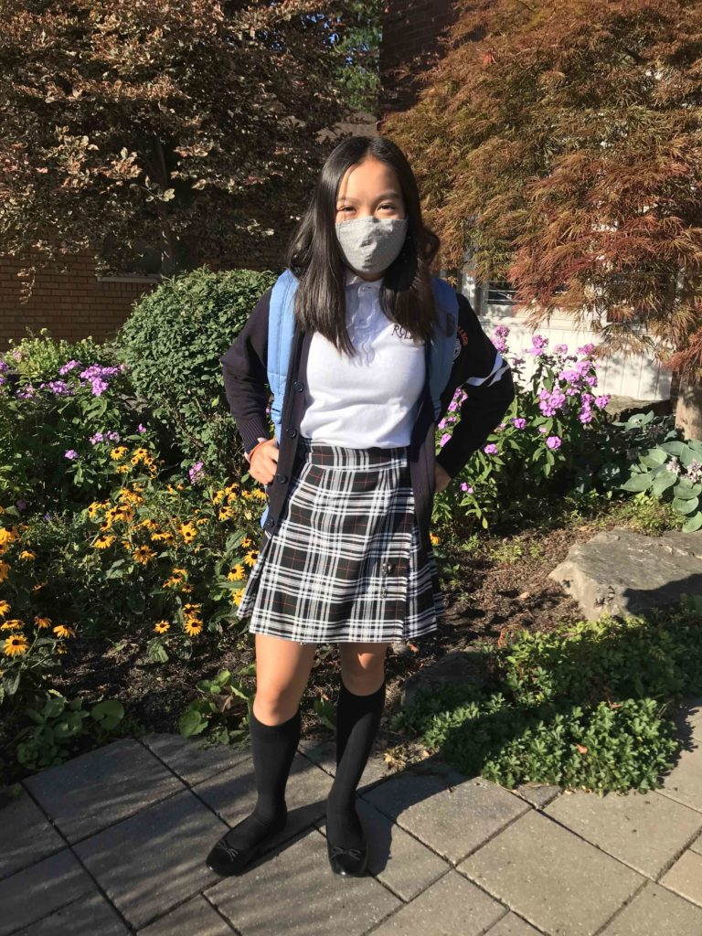 A masked female student poses in uniform with her backpack.