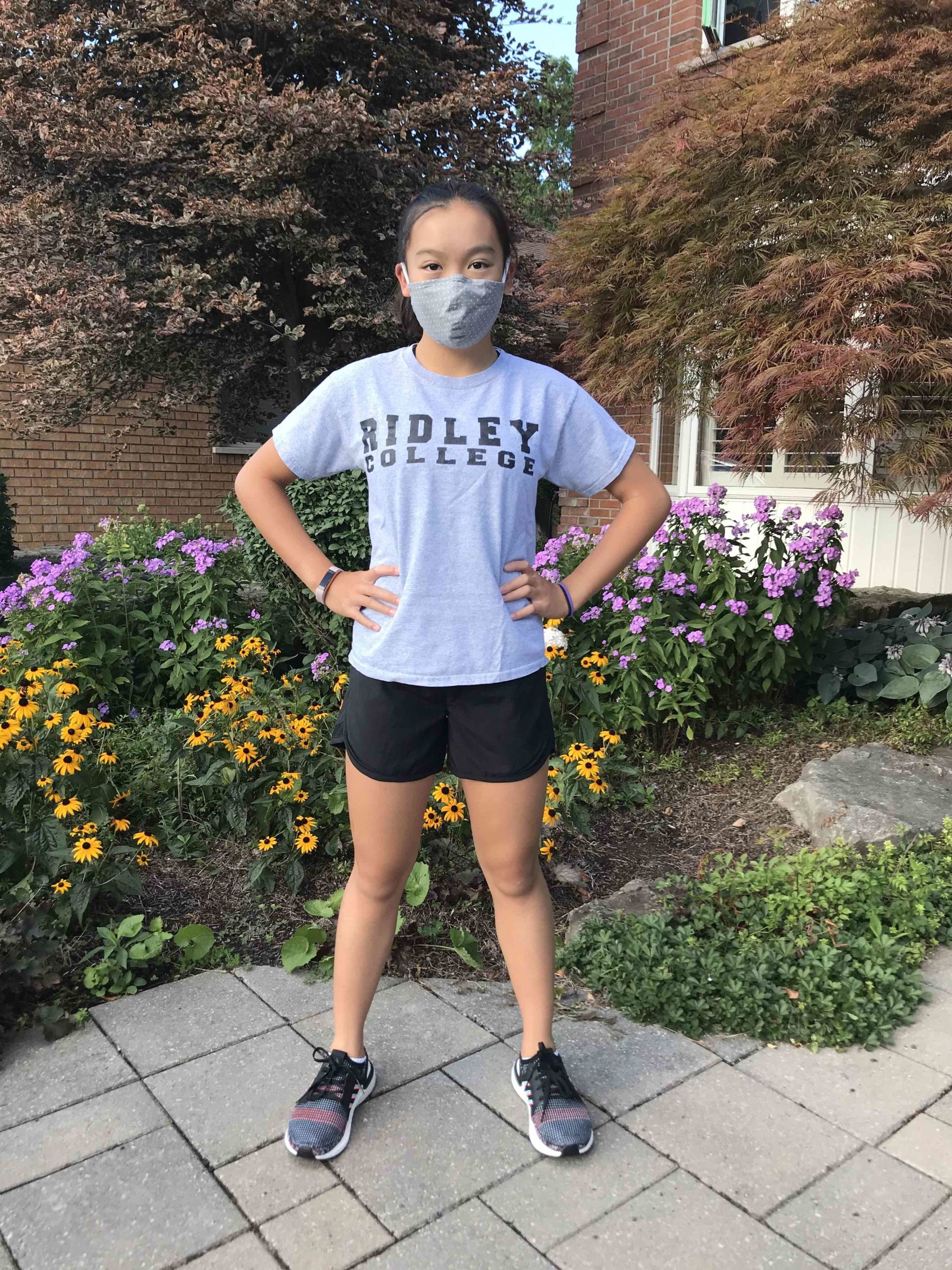 A female student in activewear poses with her mask.