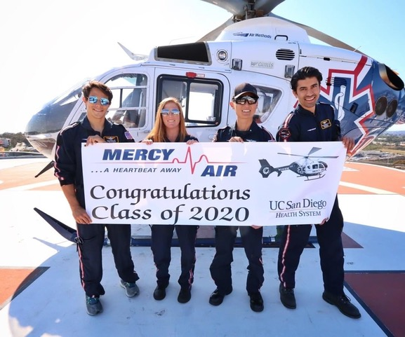 "Dr. Sam McGlone holding a sign with three fellow graduates standing in front of a helicopter. Sign says ""Congratulations Class of 2020"" with a logo from the UC San Diego Health System."
