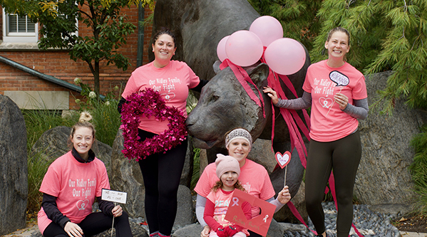 CIBC run for the cure runners pose in pink in front of tiger statue