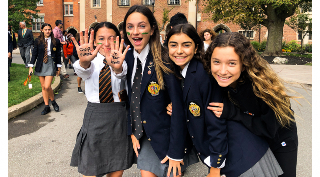 four female Ridley students with 'our future in your hands' written on their palms